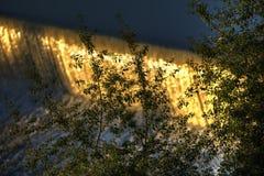 Innaffi la cascata sul fiume della Moldava a Praga durante il sole di primo mattino con vegetazione nella priorità alta Fotografia Stock Libera da Diritti