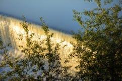 Innaffi la cascata sul fiume della Moldava a Praga durante il sole di primo mattino con vegetazione nella priorità alta Fotografia Stock
