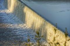 Innaffi la cascata sul fiume della Moldava a Praga durante il sole di primo mattino con vegetazione nella priorità alta Fotografie Stock