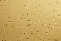 Innaffi la goccia di pioggia sul vetro dell'oro giallo per fondo fresco astratto immagine stock libera da diritti