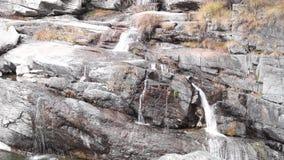 Innaffi la procedura in sequenza sopra le rocce, la cascata ed i colori di autunno negli alberi gialli e rossi delle montagne, video d archivio