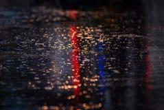 Innaffi la riflessione sulla strada con il semaforo variopinto Fotografia Stock