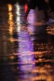 Innaffi la riflessione sulla strada con il semaforo variopinto ed il fondo pedonale di camminata Fotografia Stock
