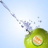 Innaffi la spruzzata sulla mela verde con il contrassegno Fotografia Stock