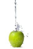 Innaffi la spruzzata sulla mela verde isolata su bianco Immagini Stock