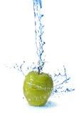 Innaffi la spruzzata sulla mela verde isolata su bianco Fotografia Stock