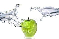 Innaffi la spruzzata sulla mela verde isolata su bianco Immagine Stock