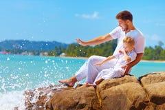 Innaffi la spruzzatura sul padre e sul figlio felici sulla vacanza Fotografia Stock