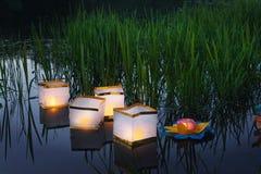 Innaffi le lanterne gialle brucianti sul lago in mezzo di erba alta Fotografia Stock