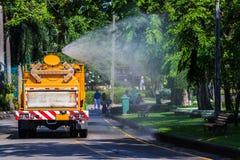 Innaffiando nel parco pubblico con il grande spruzzatore del carro armato che mostra acqua vaporizzata Immagine Stock