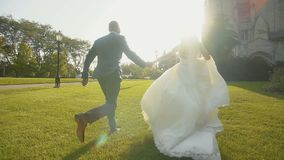 Innamorandosi sposa e sposo che si tengono per mano insieme e che corrono vicino al palazzo grande il giorno soleggiato archivi video