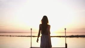 Innegrej härlig kvinna med brunt hår i elegant grå siden- klänning som går på en pir solljus Ovanför havet stock video