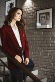 Innegrej- och brunettmodellflicka med ljus makeup, i det stilfulla omslaget, i blusen och i det moderiktigt arkivfoton