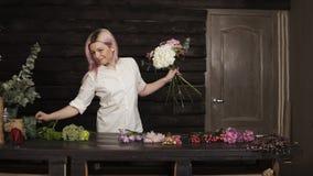 Innegrej som ler flickablomsterhandlaren i processen av garnering en bukett av blommor långsam rörelse inomhus arkivfilmer