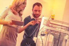 Innehållen mogen kvinna och hennes assistent som lär att fungera en skrivare 3D tillsammans royaltyfri foto