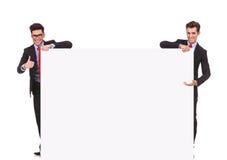 Innehav för två affärsmän som ett stort tomt undertecknar arkivbilder