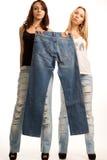 Innehav för två flickor upp en para av jeans Arkivfoton