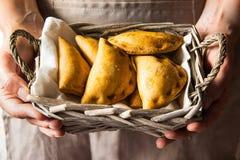 Innehav för ung kvinna i vide- korg för händer med nytt bakade empanadasomsättningpajer med grönsakkinfolken arkivbilder
