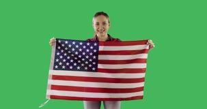 Innehavamerikanska flaggan för vuxen kvinna med polen, stjärnor och bandet på den nyckel- gröna skärmen för chroma stock video