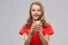 Innehavet för den tonårs- flickan kan av sodavatten med papperssugrör royaltyfria bilder