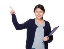 Innehavet för den unga kvinnan med skrivplattan och fingret pekar upp Arkivfoto