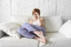 Innehavet för den unga kvinnan som gör ont period för kramp för buklidandemage, smärtar Royaltyfri Foto