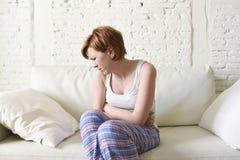 Innehavet för den unga kvinnan som gör ont period för kramp för buklidandemage, smärtar arkivfoto