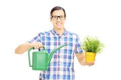 Innehavet för den unga mannen som bevattnar kan och blomkrukan Arkivbild