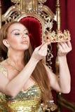 Innehavkrona för ung kvinna drottning Royaltyfria Bilder