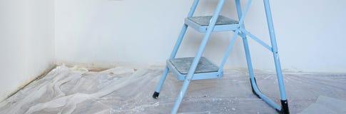 Innenansicht der Baustelle, der Leiter im Vordergrund und der frischen malenden Wände mit weißer Farbe lizenzfreie stockbilder