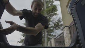 Innenansichtauto des glücklichen Öffnungsstammes des jungen Mannes und ladendes Reisegepäck für Ferien - stock video footage