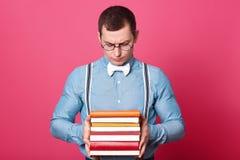 Innenatelieraufnahme der dunkelhaarigen verwirrten Modellaufstellung lokalisiert über dem hellen rosa Hintergrund, Bücher in sein stockfoto