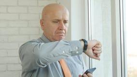 Innenbüro-Geschäftsmann-Image Checking Hand-Uhr für ein Geschäftstreffen stockfoto