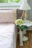 Innenbettraum mit Vasenblume und -lampe Stockfotos