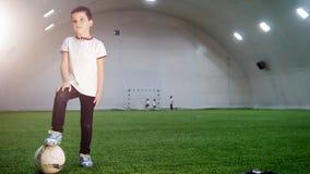 Innenfußballarena Eine Stellung des kleinen Jungen mit dem Setzen des Beines auf den Ball stock video footage