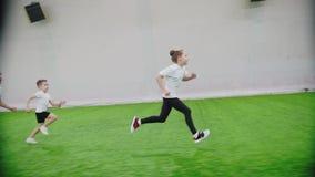 Innenfußballarena Kinder, die auf dem Feld laufen Ein Mädchen führt den Ball stock footage