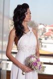 Innenporträt der entzückenden Braut mit dem schwarzen langen Haar vor Fenster Stockbilder