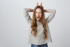 Innenporträt der schönen jungen europäischen Frau, die, Finger hinter Kopf halten blinzelt, als ob, die Ohren, glaubend nachahmen Lizenzfreie Stockfotos