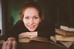 Innenporträt von Studentenfrauenlernen- oder -lesebüchern der Rothaarigen glücklichen lizenzfreie stockfotos