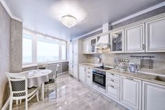 Innenraum der weißen hölzernen Küche in einer geräumigen Wohnung in den hellen Farben Stockbild