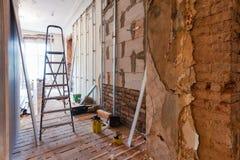 Innenraum der Wohnung mit Materialien während auf der Erneuerung, die Wand von der Gipsfasergipsplatte herstellt lizenzfreies stockfoto