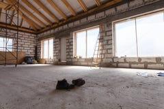 Innenraum der Wohnung während der Untererneuerung, die Umgestaltung und der Bau ein Paare Funktionsschuhe auf dem Zement breitet  stockfoto