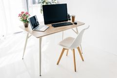 Innenraum des Arbeitsplatzes mit Stuhl, Blumen, Kaffee, Briefpapier, Laptop und Computer stockbild