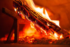 Innenraum des hölzernen abgefeuerten Ziegelsteinofens mit brennendem Klotz Stockfotografie