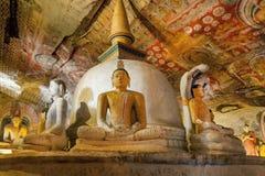Innenraum des historischen Höhlentempels mit stützenden Gautama Buddha-Zahlen und gemalte Wände und Fresko Stockbilder