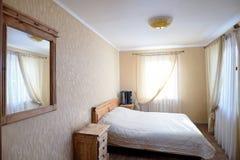 Innenraum des Schlafzimmers des ländlichen Hauses mit Bayan auf Nightstand Lizenzfreie Stockbilder