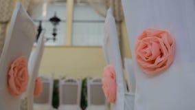 Innenraum einer Hochzeitshallendekoration bereit zu den Gästen Netter Dekor mit rosa Rosen auf weißen Stühlen stock video