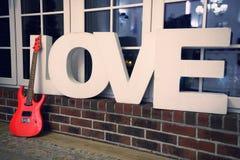 Innenraum für Valentinstag mit großen Buchstaben und roter Gitarre Lizenzfreie Stockfotos