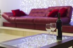 Innenraum mit einem Couchtisch, einem Sofa und einer Flasche Wein Stockfoto