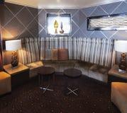 Innenraum mit modernem und stilvollem Design mit Sofaecke mit Kissen und niedrigen zeitgenössischen Stühlen Lizenzfreies Stockbild